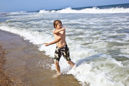 boy in motion at the rough sea photo