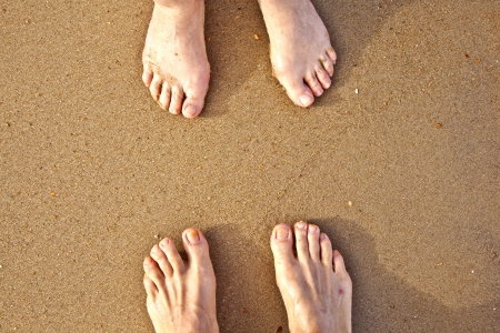 outerbanks: feet of a couple at the sandy beach