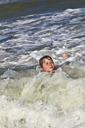 child has fun in the waves of the ocean photo