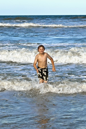 happy young boy running through the water at the beach photo