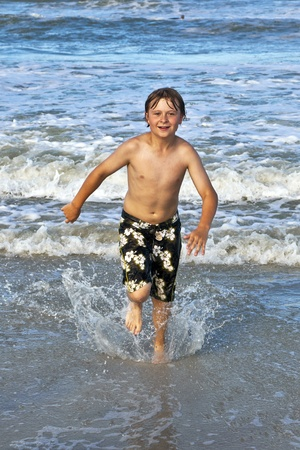 wet suit: happy young boy running through the water at the beach