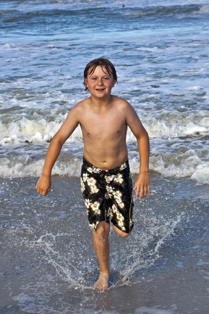 happy young boy running through the water at the beach Stock Photo - 9222645