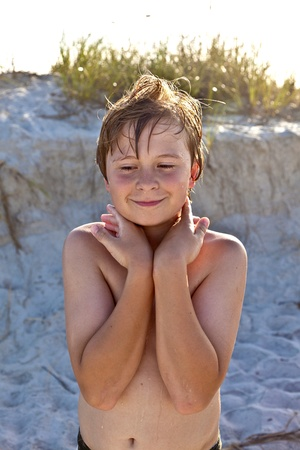 young happy smiling boy at the beach with wet hair after swimming photo