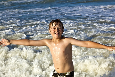 young happy boy enjoys the waves of the blue sea photo