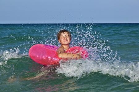 happy boy in a swim ring has fun in the ocean photo