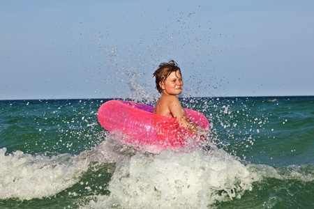 happy boy in a swim ring has fun in the ocean with waves photo