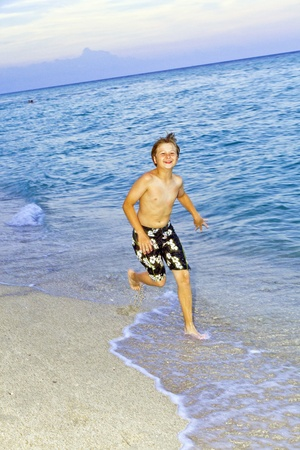 young boy is jogging at the beautiful beach Stock Photo - 9220987