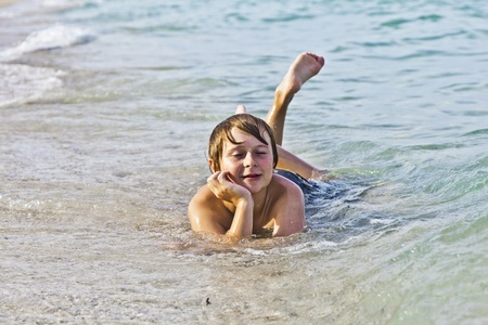 young boy enjoys lying at the beach in the surf photo