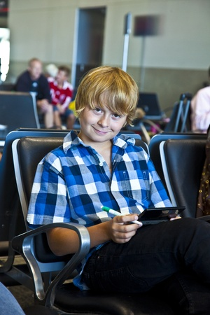 electronical: boy is waiting for departure at the airport and playing an electronical game Stock Photo