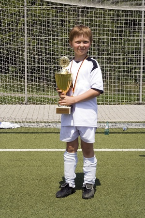 young boy in soccer dress presents proud the cup which was won by his soccer team in a tournament