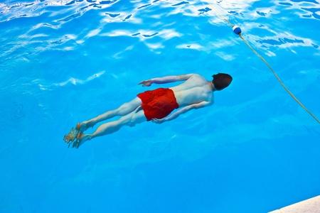 boy has fun diving in the pool photo