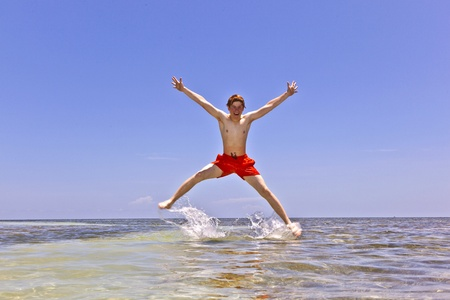 young boy jumping out of the water at the tropical beach photo