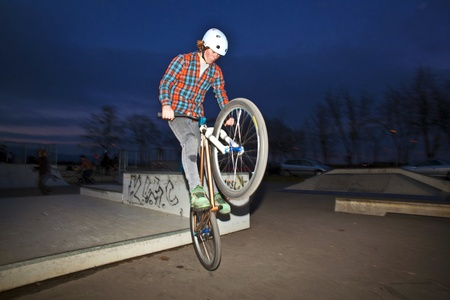 boy on his dirtbike jumping at the skate park by night photo