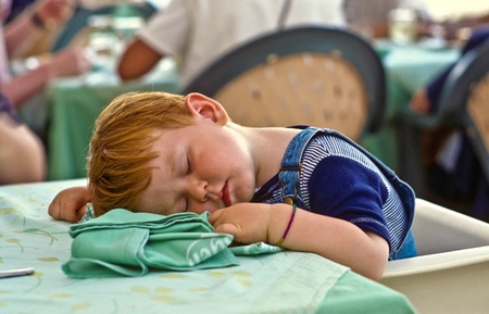 young boy falling asleep on the dinner table photo