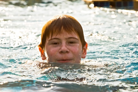 enyoing: boy with red hair is swimming in the pool and enyoing the fresh water