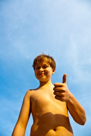 happy smiling young boy with background blue sky gives fingersign all-right, thumbs-up Stock Photo - 9223504