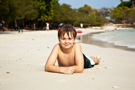 boy is lying at the beach and enjoying the warmness of the water and looking self confident and happy Stock Photo - 9222855