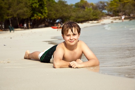 boy is lying at the beach and enjoying the warmness of the water and looking self confident and happy Stock Photo - 9221478