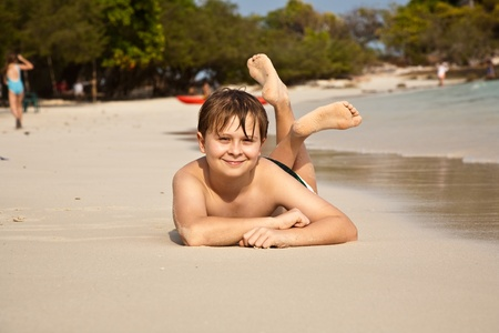 sun bathing: boy iy lying at the beach and enjoying the warmness of the water and looking self confident and happy