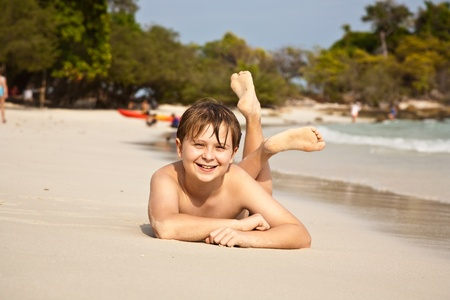 boy is lying at the beach and enjoying the warmness of the water and looking self confident and happy Stock Photo - 9221434