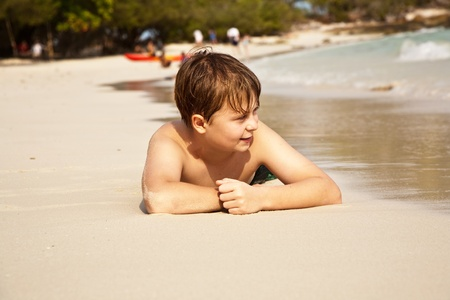boy iy lying at the beach and enjoying the warmness of the water and looking self confident and happy Stock Photo - 9222858