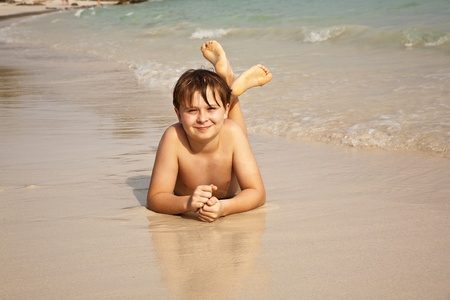 boy is lying at the beach and enjoying the warmness of the water and looking self confident and happy photo