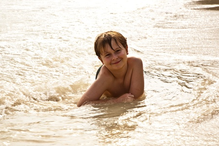 boy iy lying at the beach and enjoying the warmness of the water and looking self confident and happy Stock Photo - 9223870