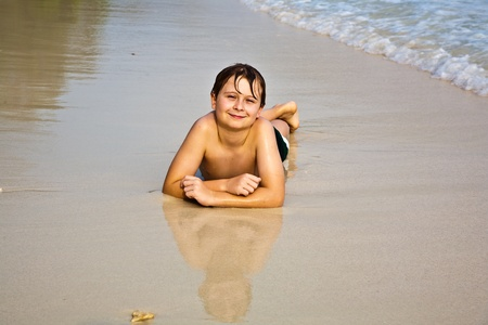 young boy is lying at the beach and enjoying the warmness of the water and looking self confident and happy Stock Photo - 9221603