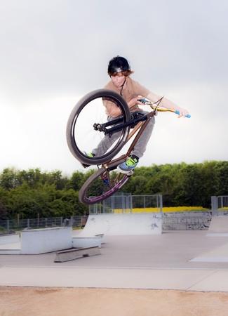 stunts: giovane ragazzo andando airborne con la sua moto