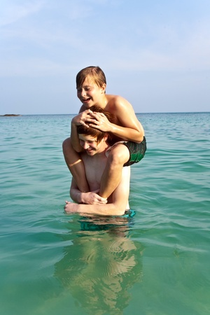 brothers are playing together in a beautiful sea with crystal clear water and blue sky photo