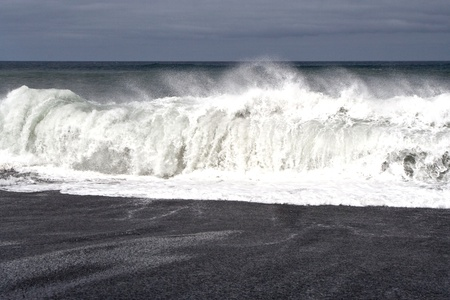 heavy waves with white wave crest in storm at the beach from Janubio, a volcanic black beach, Lanzarote, Spain photo