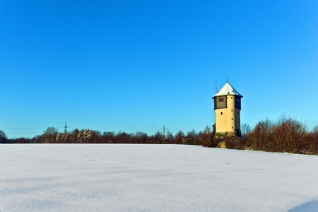 covered fields: watertower in winter with snow covered fields Stock Photo