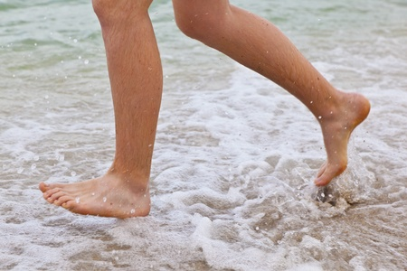 foot marks: feet of boy running along the beach in the water Stock Photo