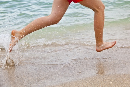 feet of boy running along the beach in the water photo