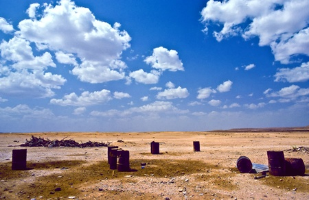 desert in South Yemen is polluted by rusty ballels of oil photo