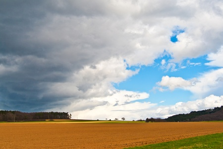 dark clouds and blue sky over fields Stock Photo - 9288262