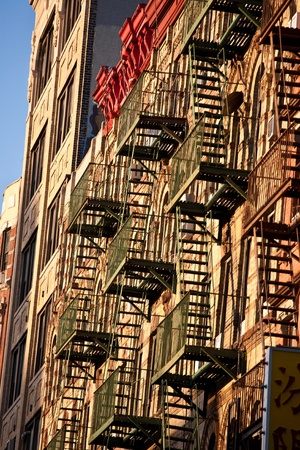 old iron fire escape rescue ladders at old houses in beautiful light photo