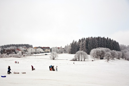 children are skating at a toboggan run in winter on snow photo