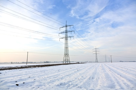 electrical tower in wintertime with snow covered fields photo