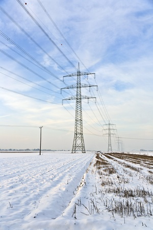 covered fields: electrical tower in wintertime with snow covered fields Stock Photo