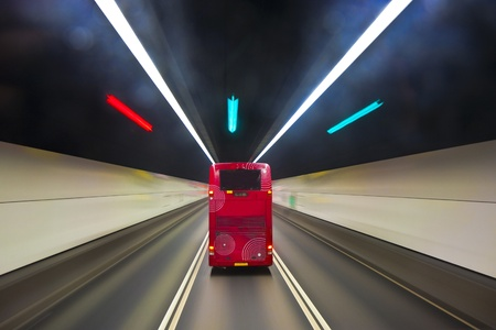 beautiful red english bus in a tunnel in Hongkong with light effects from tunnel light and street markers photo