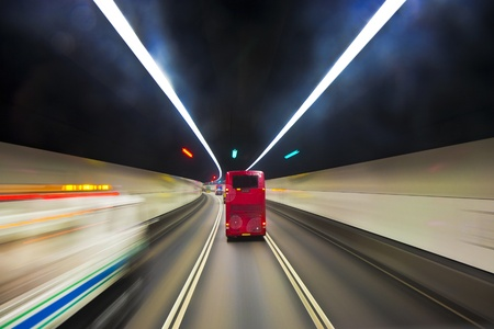english bus: beautiful red english bus in a tunnel in Hongkong with light effects from tunnel light and street markers Stock Photo