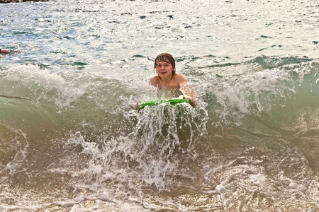 boy has fun with the surfboard at the beach photo