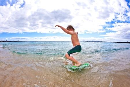 surf board: cute boy has fun at the beach