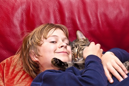 snugly: young boy is hugging with his cat at the sofa Stock Photo