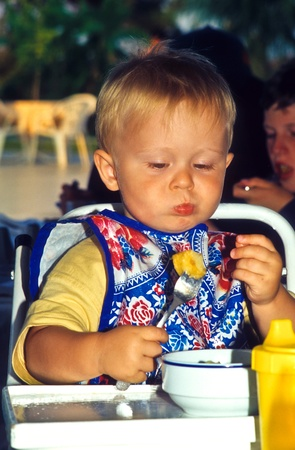 young boy eating in a children safety seat Stock Photo - 9323540
