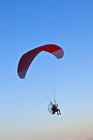 Paraglider flying over the beach with a paramotor photo