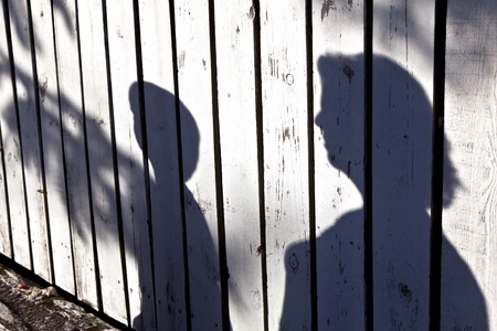 woman shadow: shadow of a boy with mother at a wooden fence