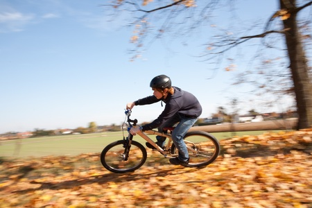 young boy is riding with the dirtbike and racing in the landscape downhill photo