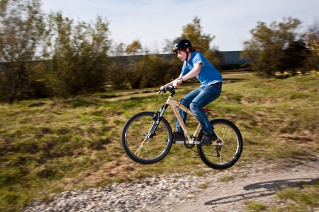 boy jumps with his dirt bike over natural ramps in open area and enjoys racing Stock Photo - 9400763
